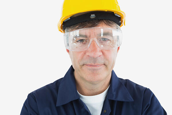 Close-up portrait of mature technician wearing protective glasses and hardhard over white background