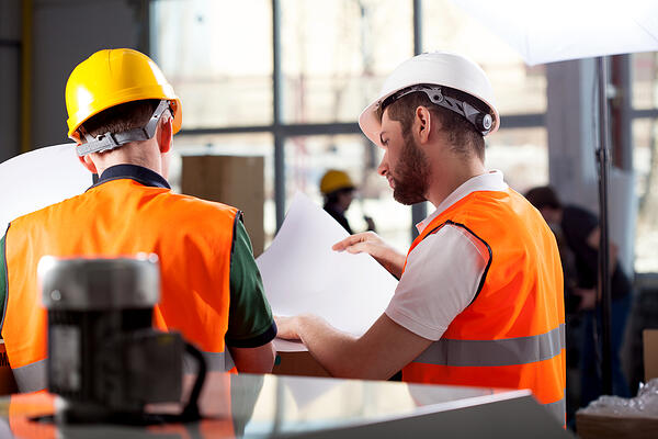 Male factory worker and supervisor are analyzing plans-1