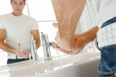 Male washing hands in sink.