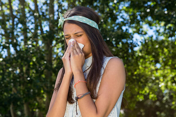 Pretty brunette blowing her nose on a summers day