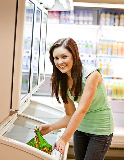 Smiling young woman holding a deep-frozen product in a supermarket