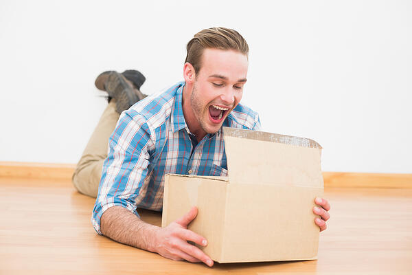 Surprised man lying on the floor opening boxe at home in the living room