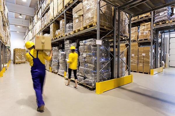 Warehouse worker with box and manager controlling products